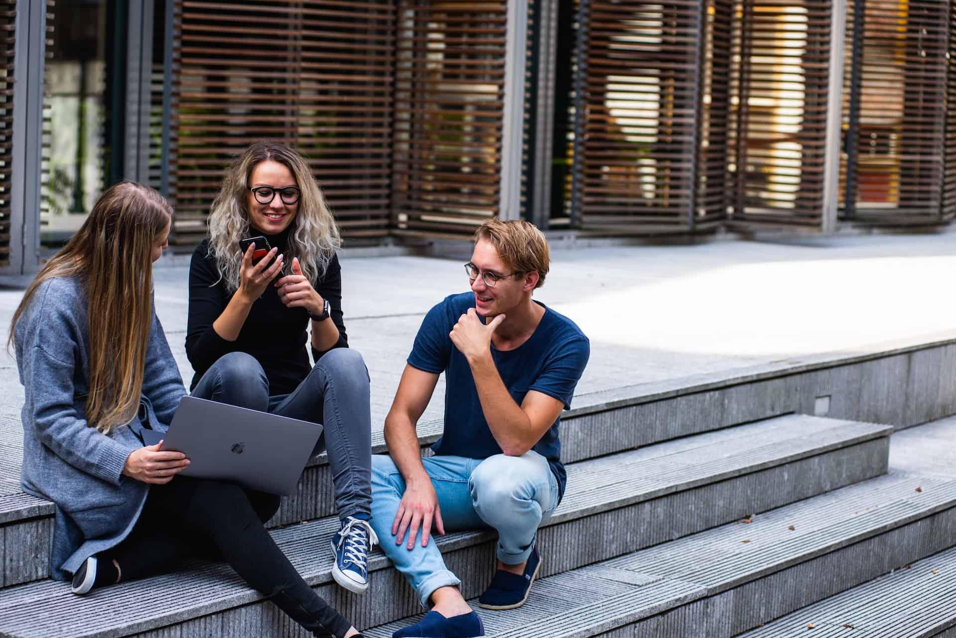 Zwei Frauen und ein Mann sitzen mit Handy und Laptop draußen auf einer Treppe (c) Pexels.com