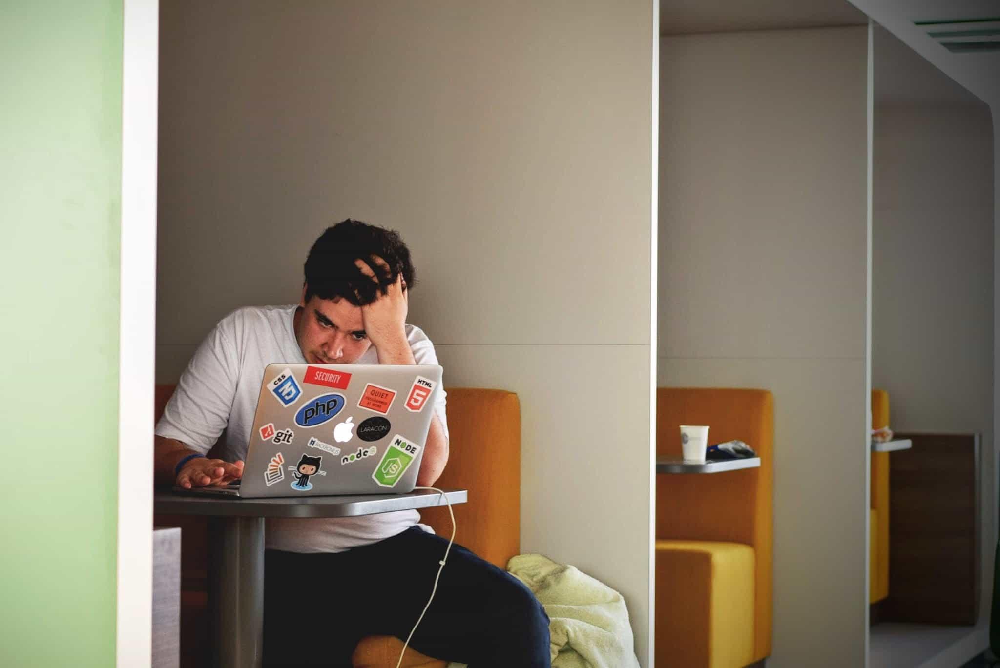 Mann sitzt verzweifel am Laptop