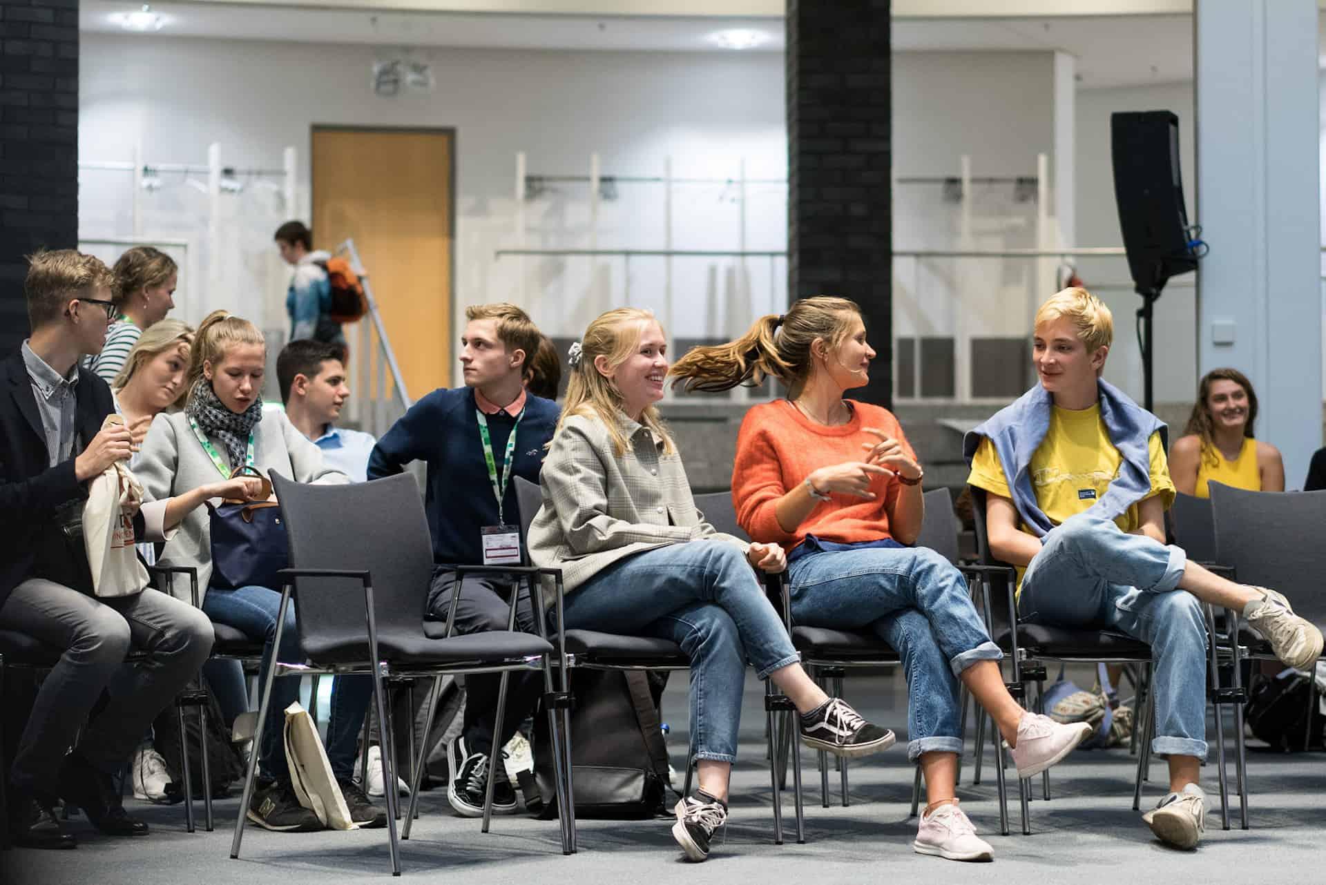 Jugendliche sitzen auf Stühlen