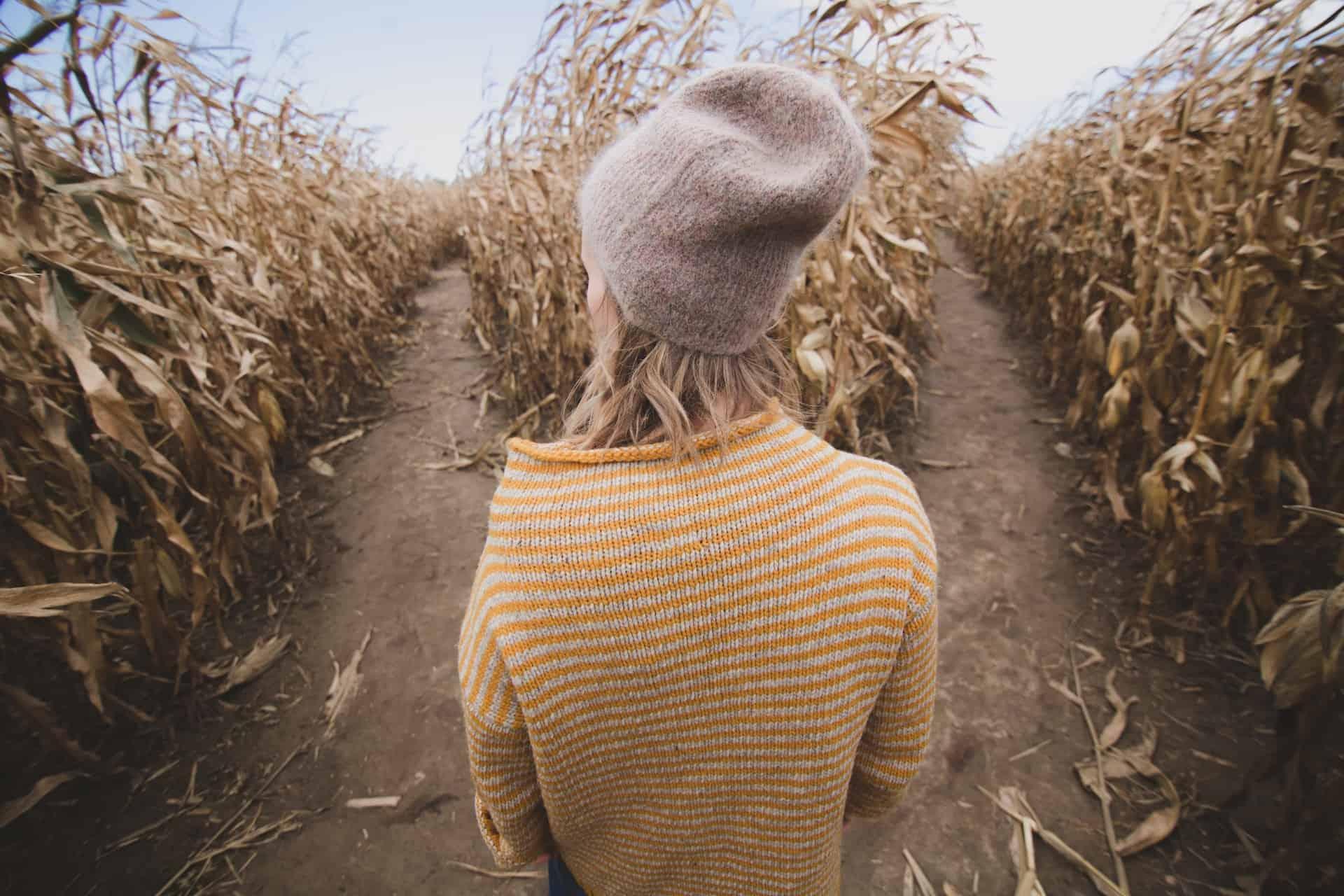 Eine Frau steht in einem Getreidefeld zwischen zwei moeglichen Wegen, die sie gehen kann.