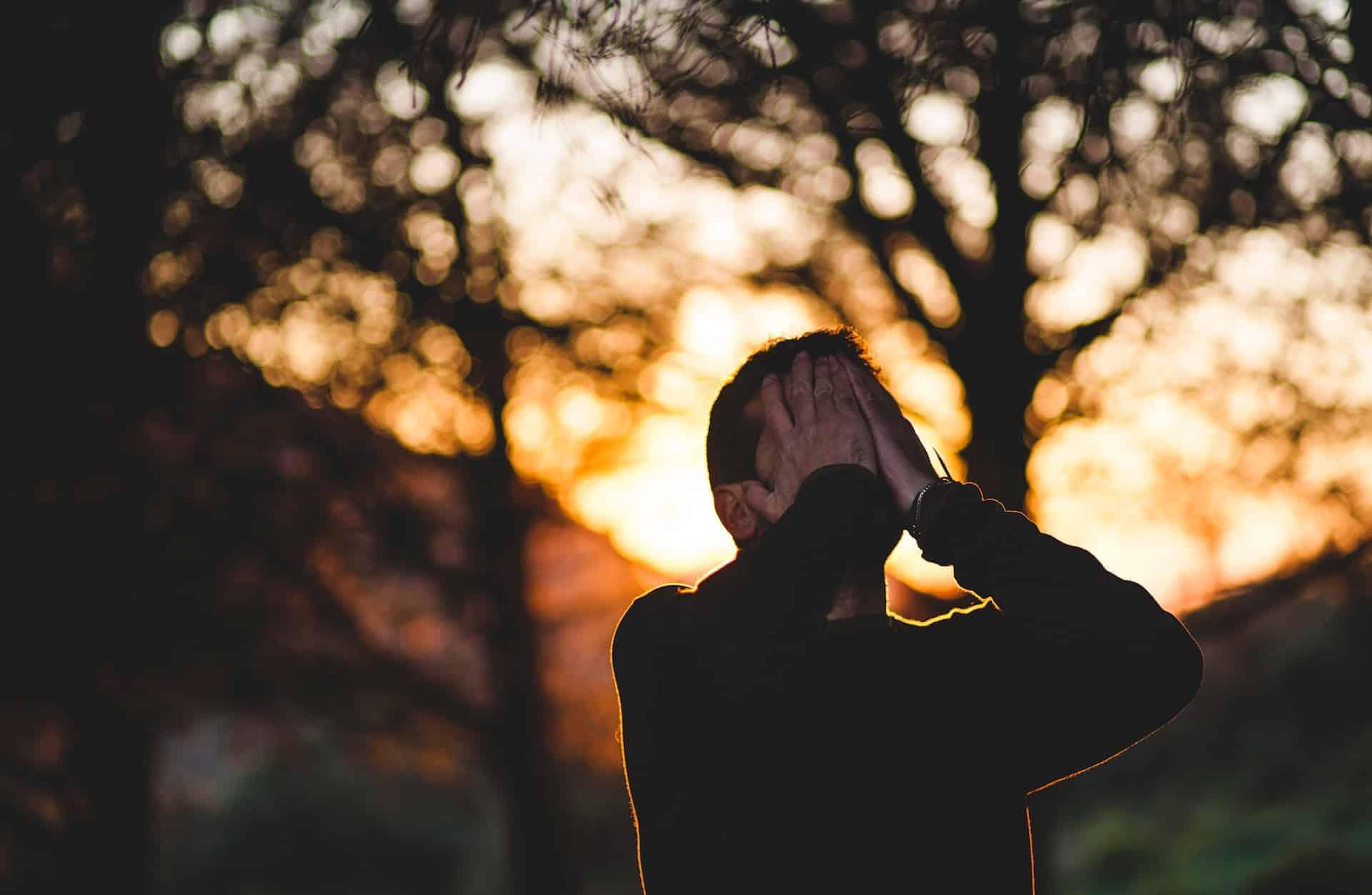 Mann verzweifel draußen im Sonnenuntergang
