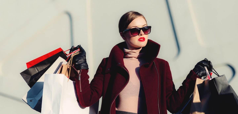 Frau mit Sonnenbrille und vielen Einkaufstueten in der Hand