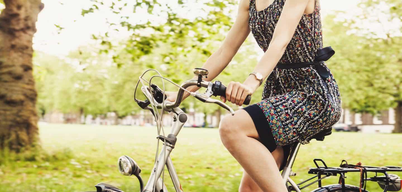 Frau auf Fahrrad im Gruenen