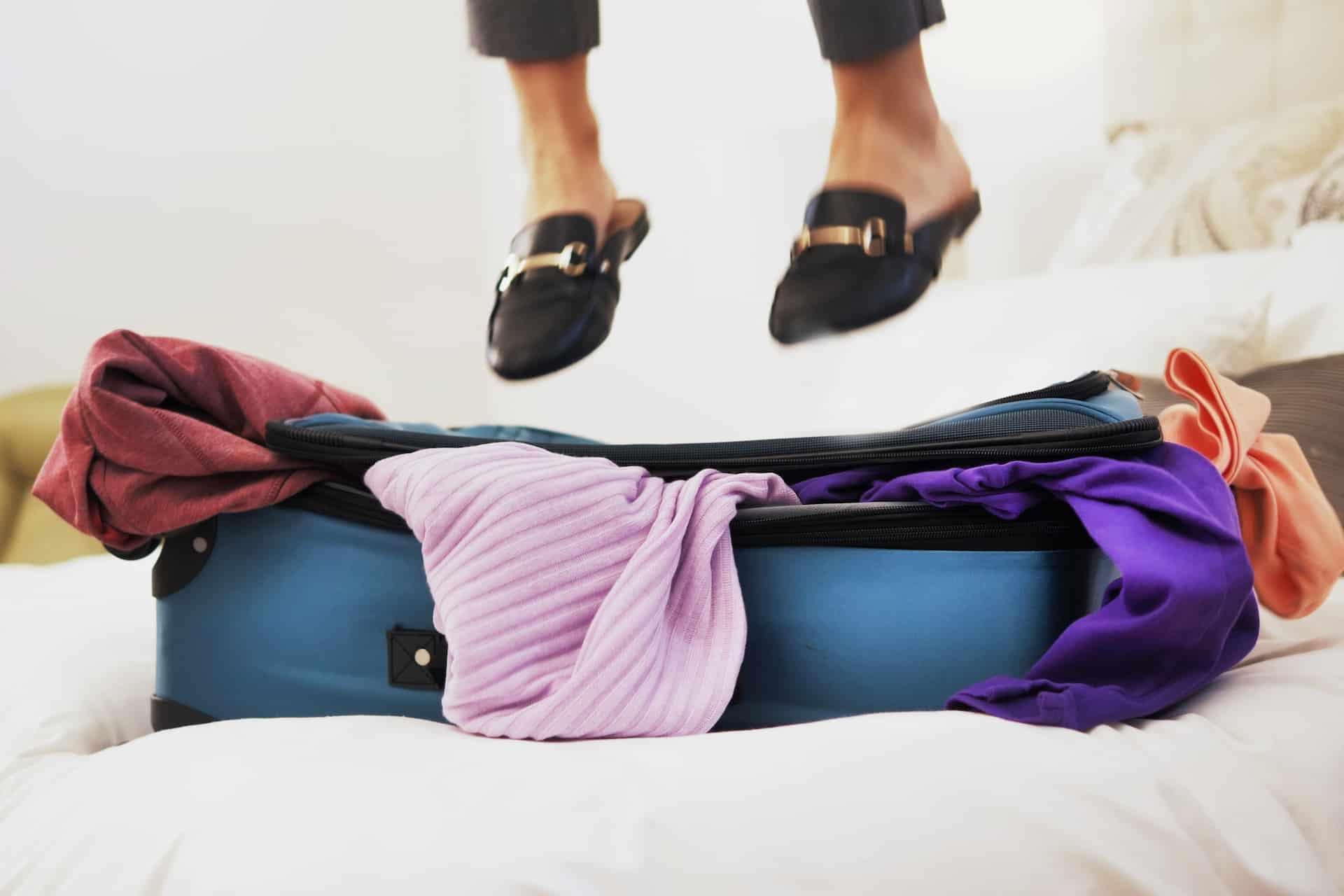 Frau springt auf Koffer