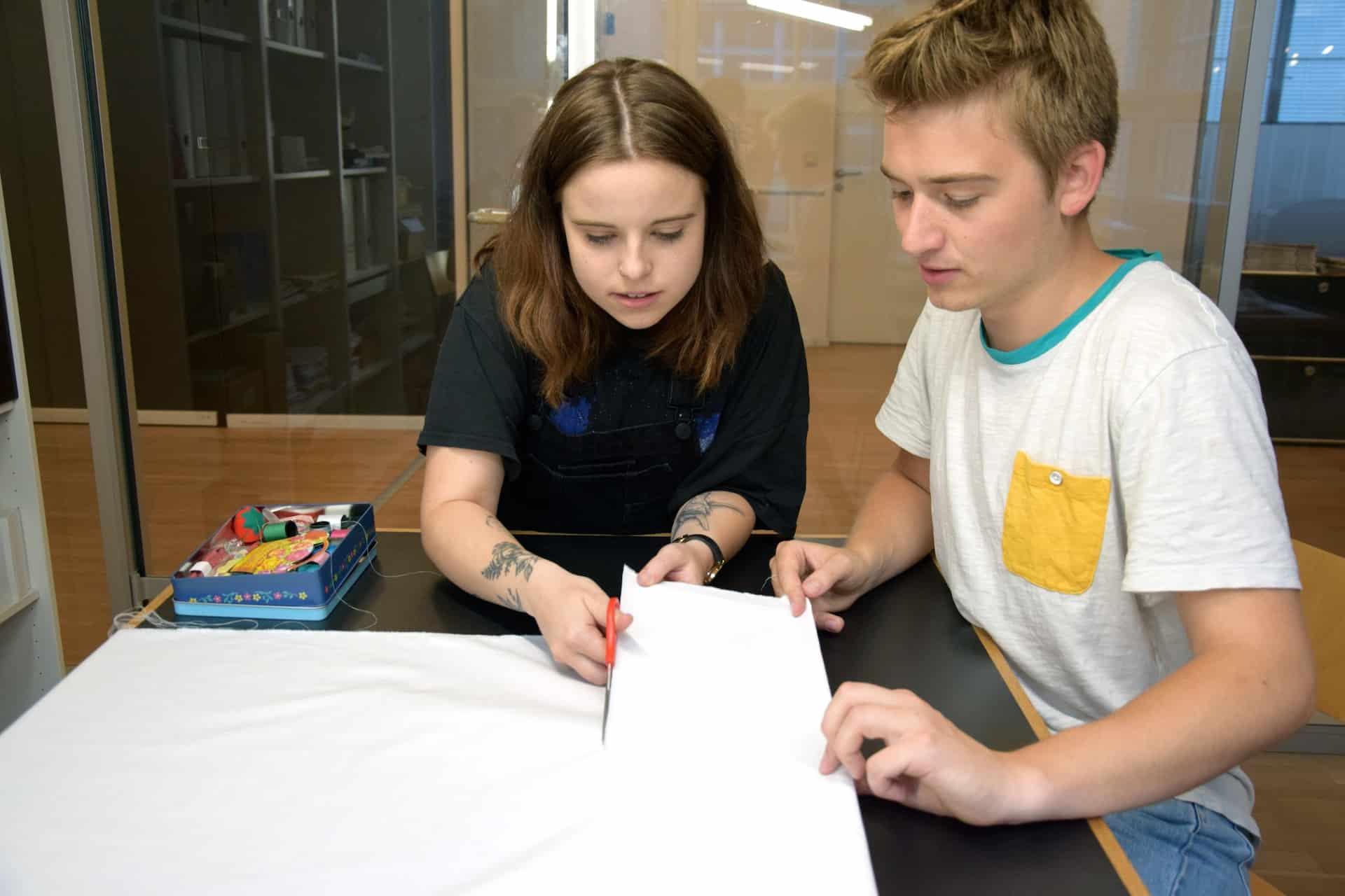 Erik und Grethe schneiden Stoff zu