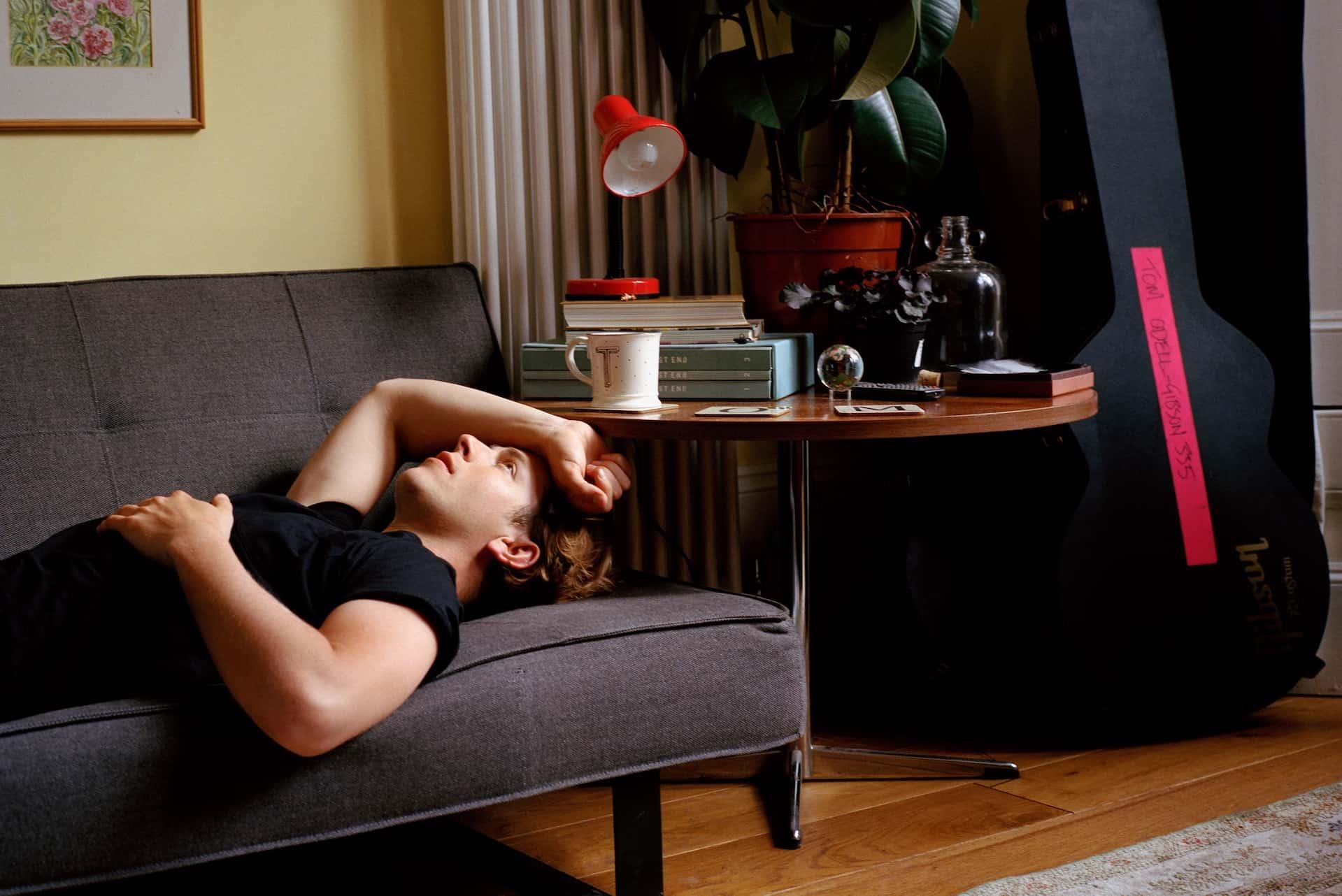 Tom Odell liegt auf einer Couch