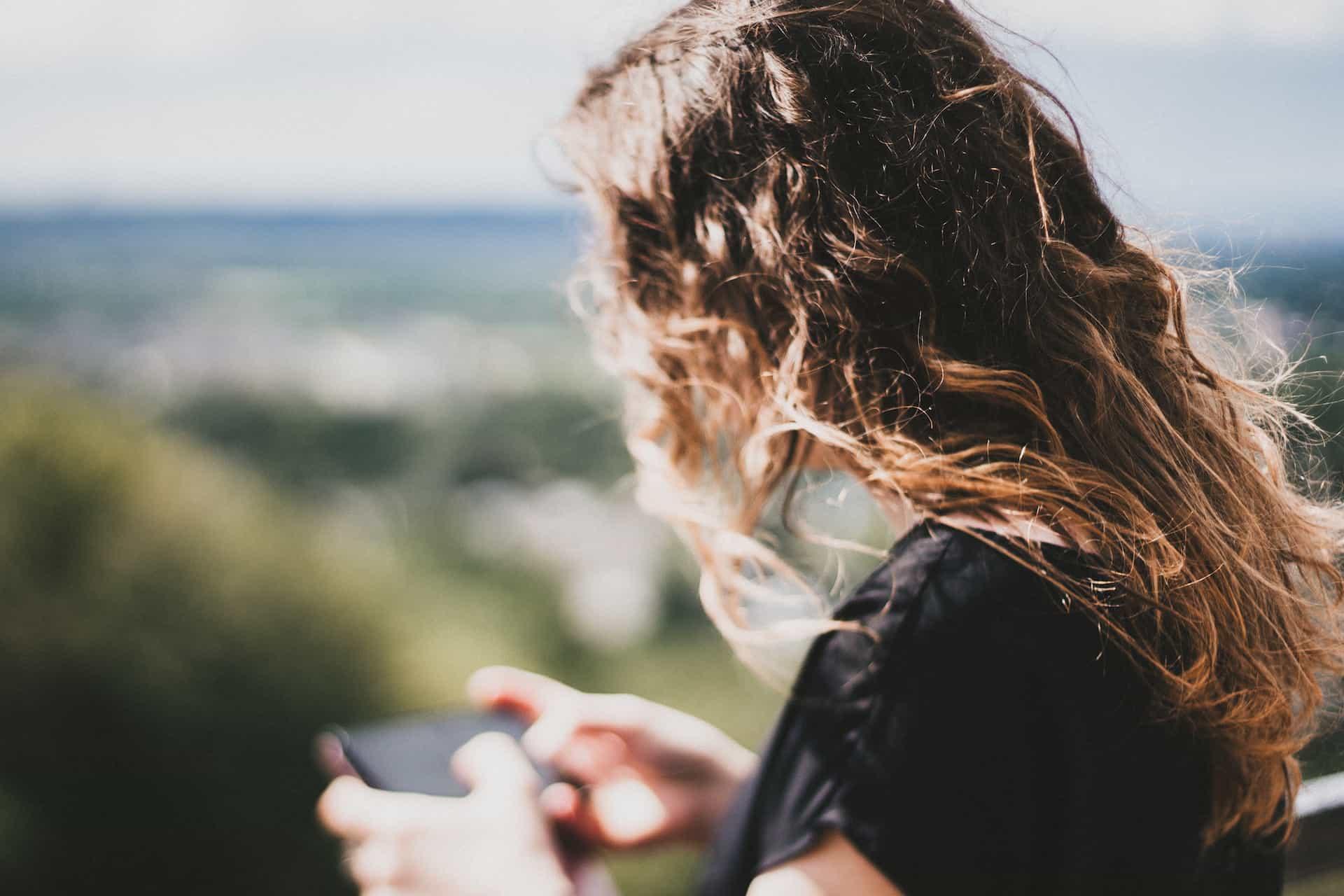 Blick ueber die Schulter einer Frau, die ein Smartphone haelt