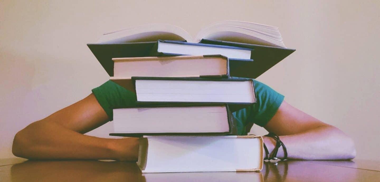 Person versteckt ihren Kopf hinter Bücherstapel