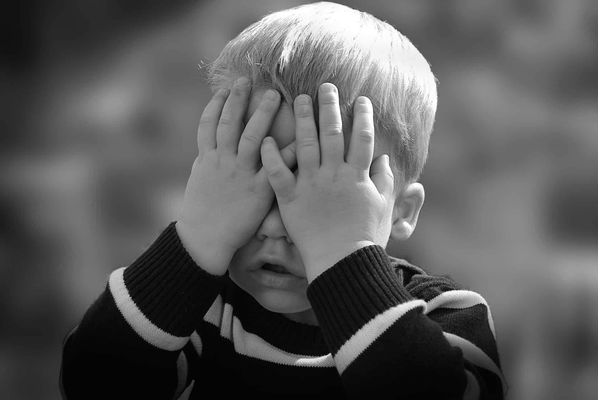 Kleines Kind schlägt sich Hände vors Gesicht