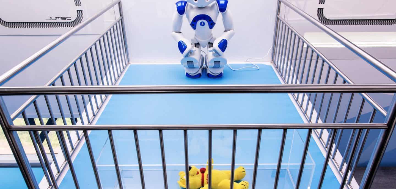 Roboter NAO steht vor einem Plüsch-Bären