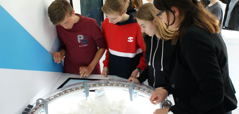 Schüler betrachten ein Experiment im TouchTomorrow Truck