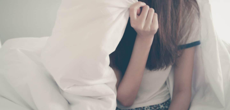 Maedchen sitzt mit Bettdecke auf Bettkante