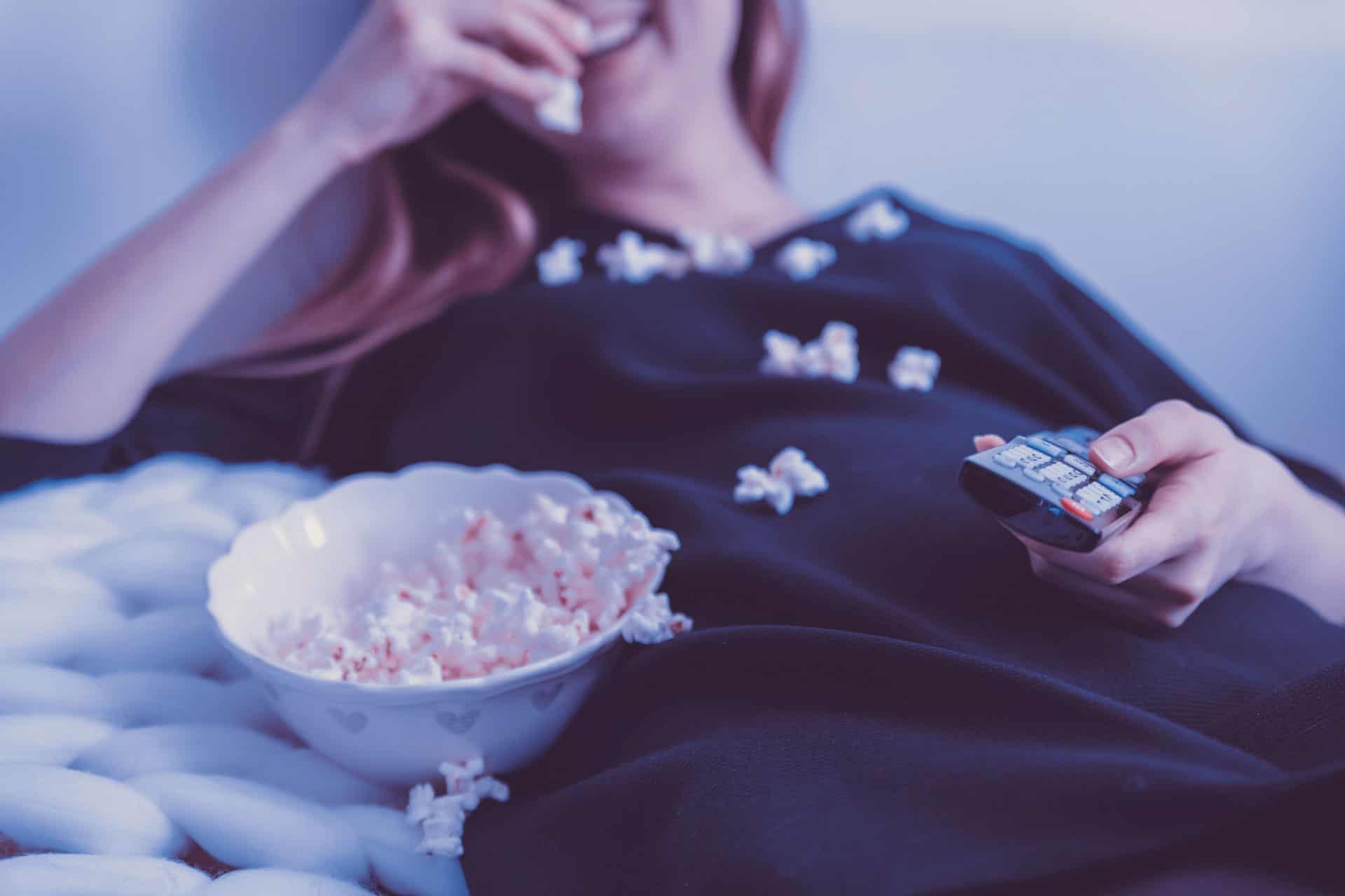 Frau isst Popcorn und schaut Netflix