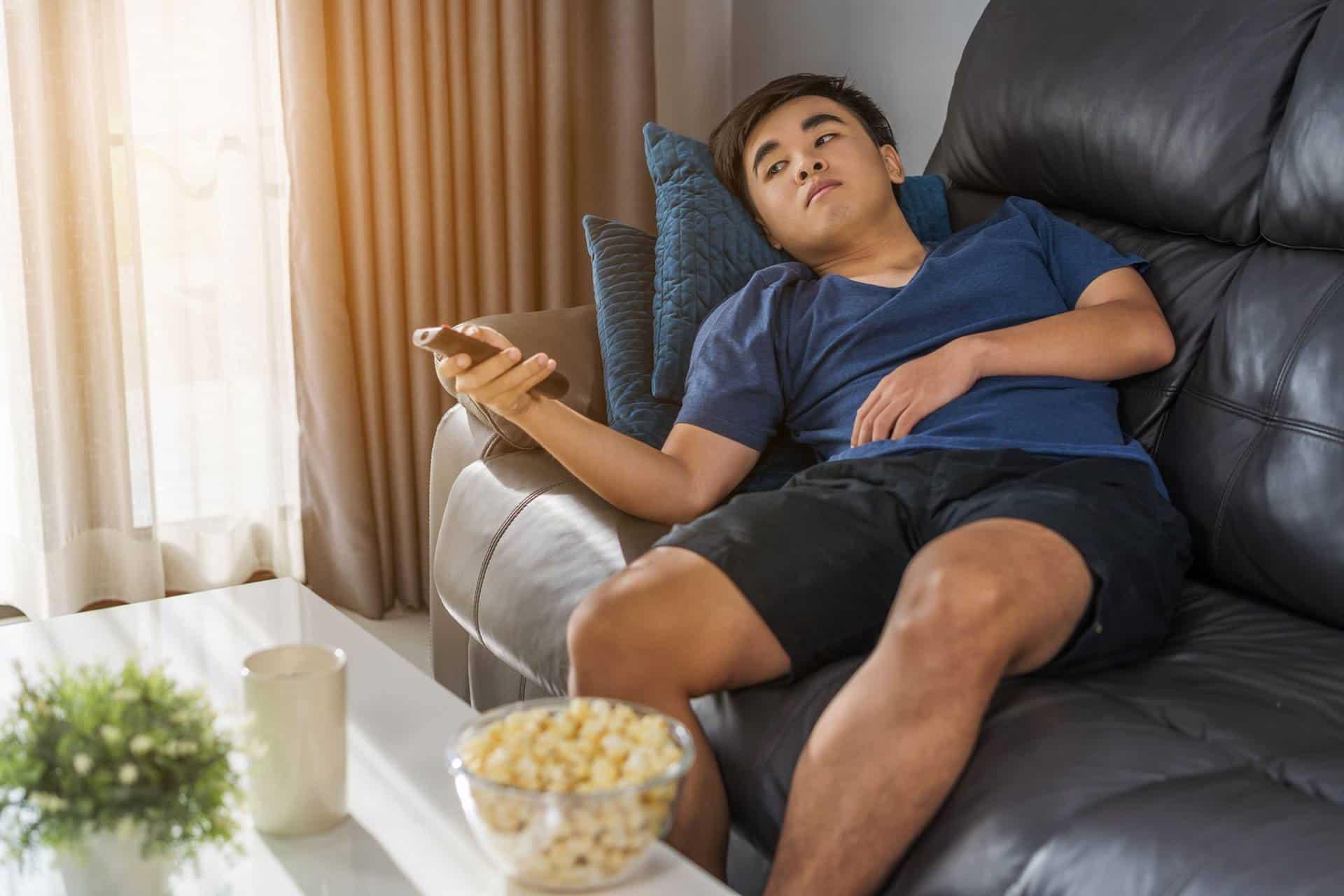 Ein junger Mann liegt gelangweilt auf der Couch. Foto: geargodz