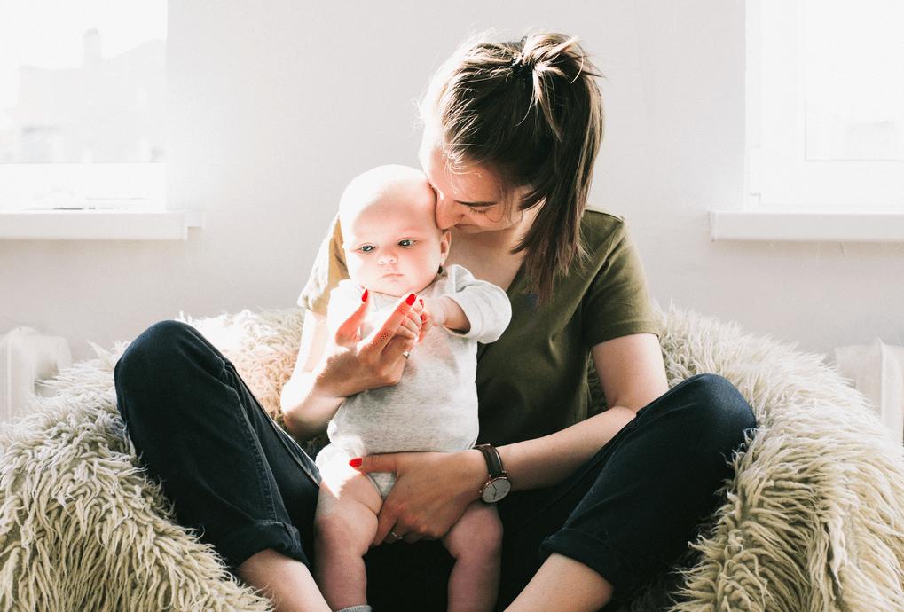 Junge Frau haelt ein Baby