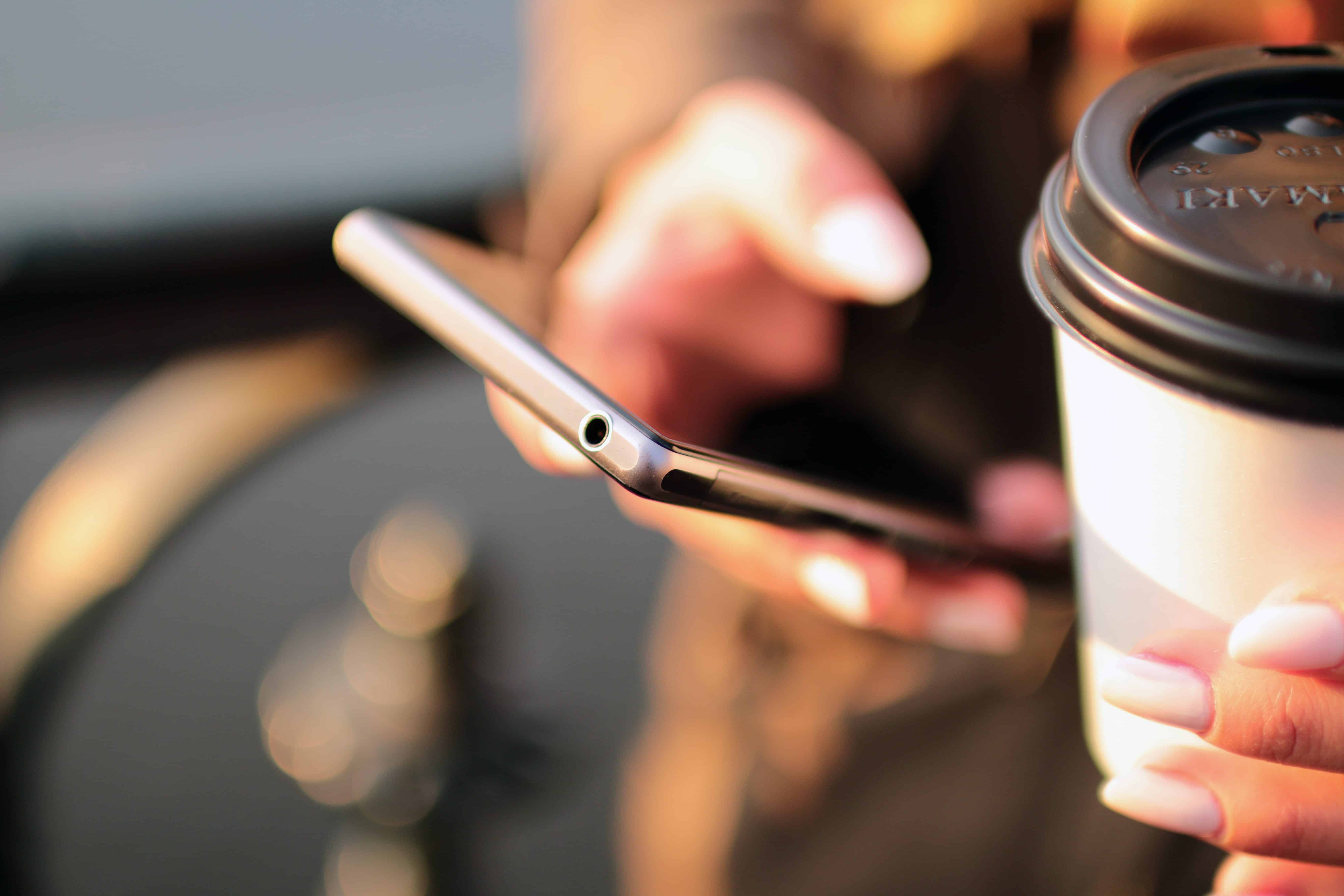 Frau haelt Kaffee und Smartphone