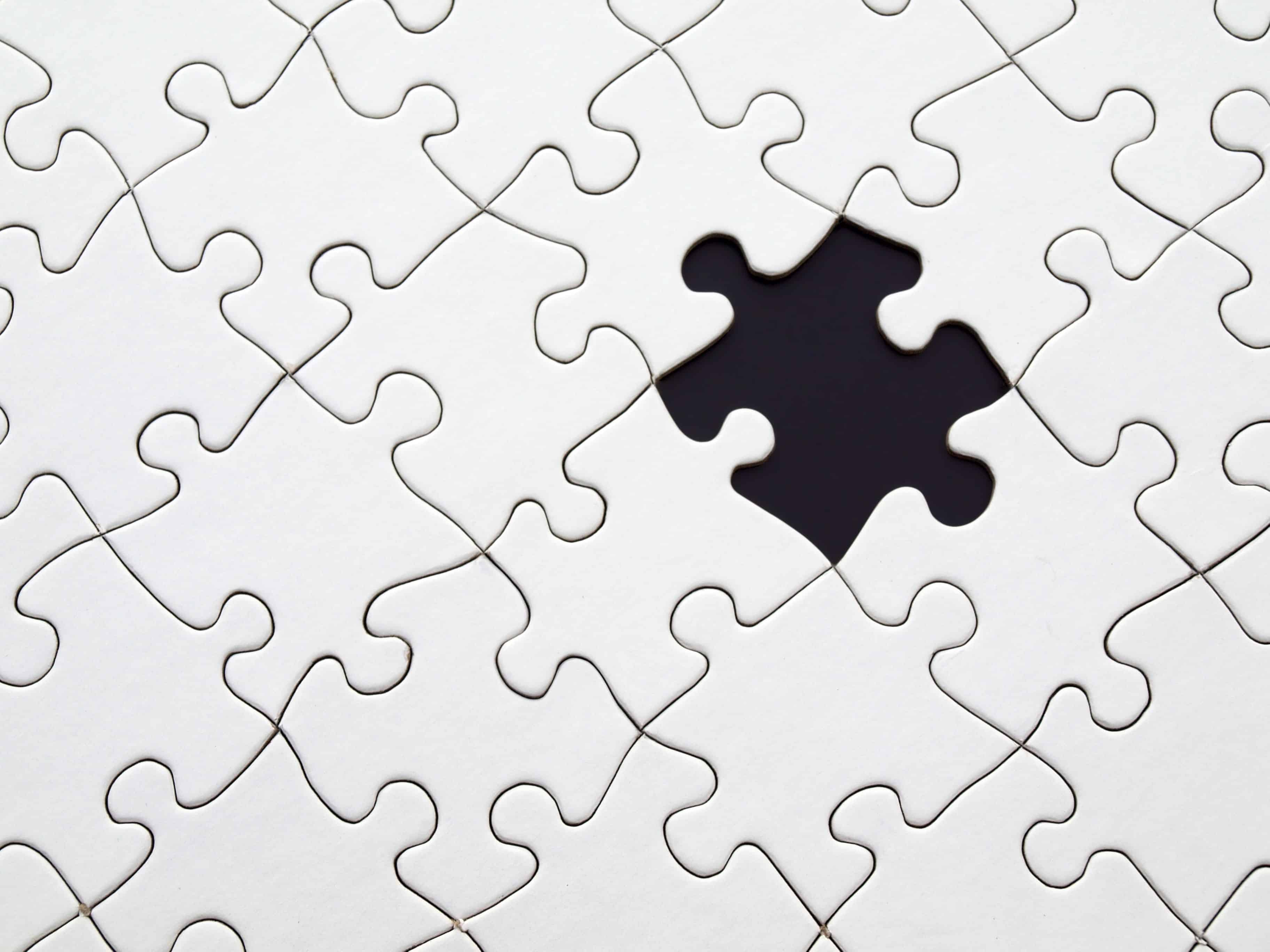 weißes Puzzle mit schwarzen Puzzle-Teil