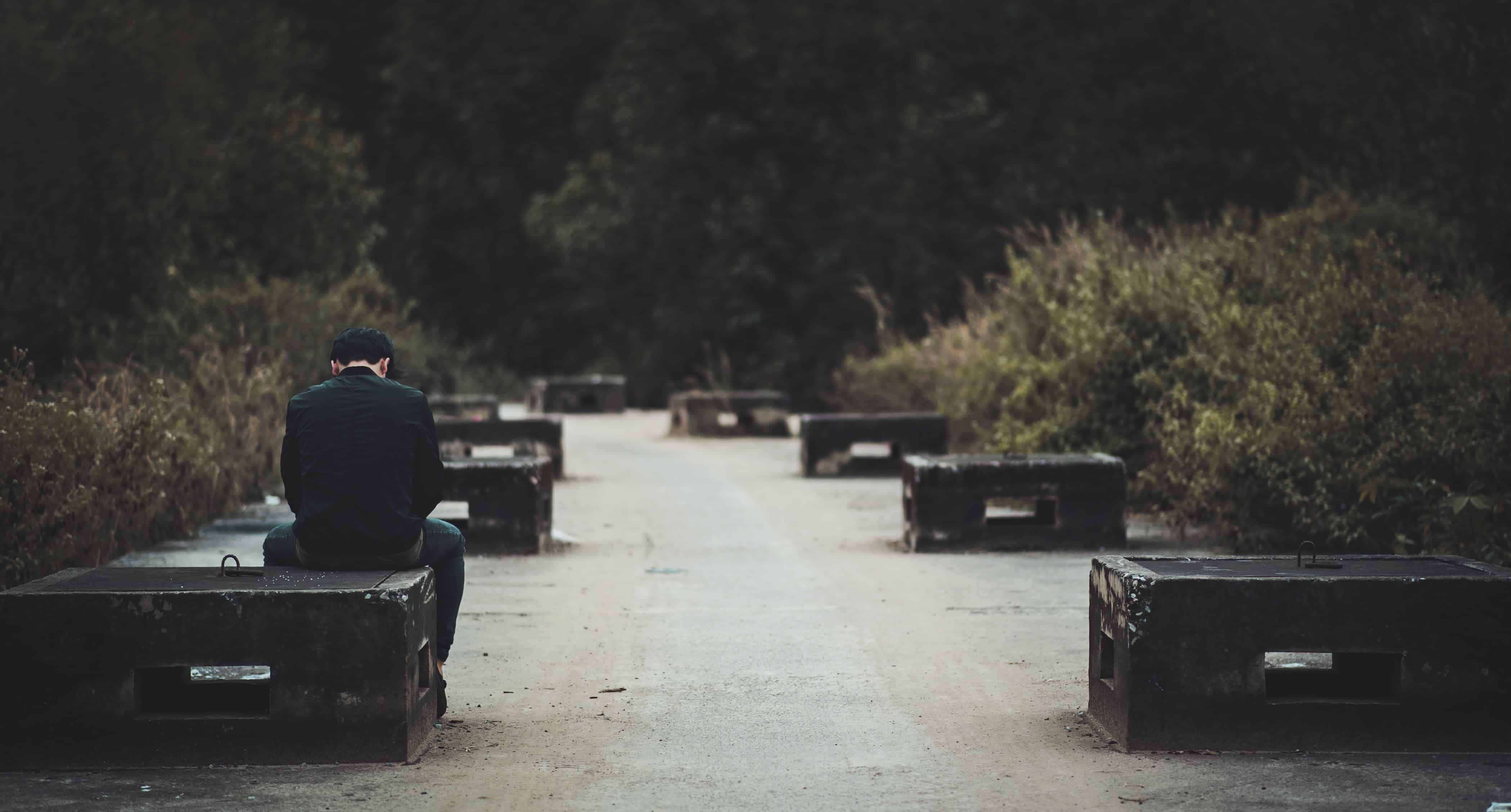 Junge sitzt traurig auf Bank