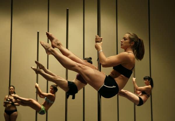Frauen turnen an Poledance-Stangen