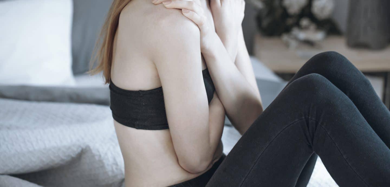 Ein sehr schlankes Mädchen sitzt auf ihrem Bett