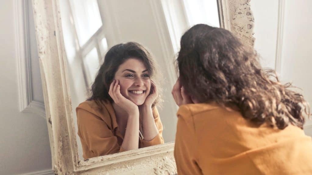 Frau bebetrachtet sich im Spiegel (