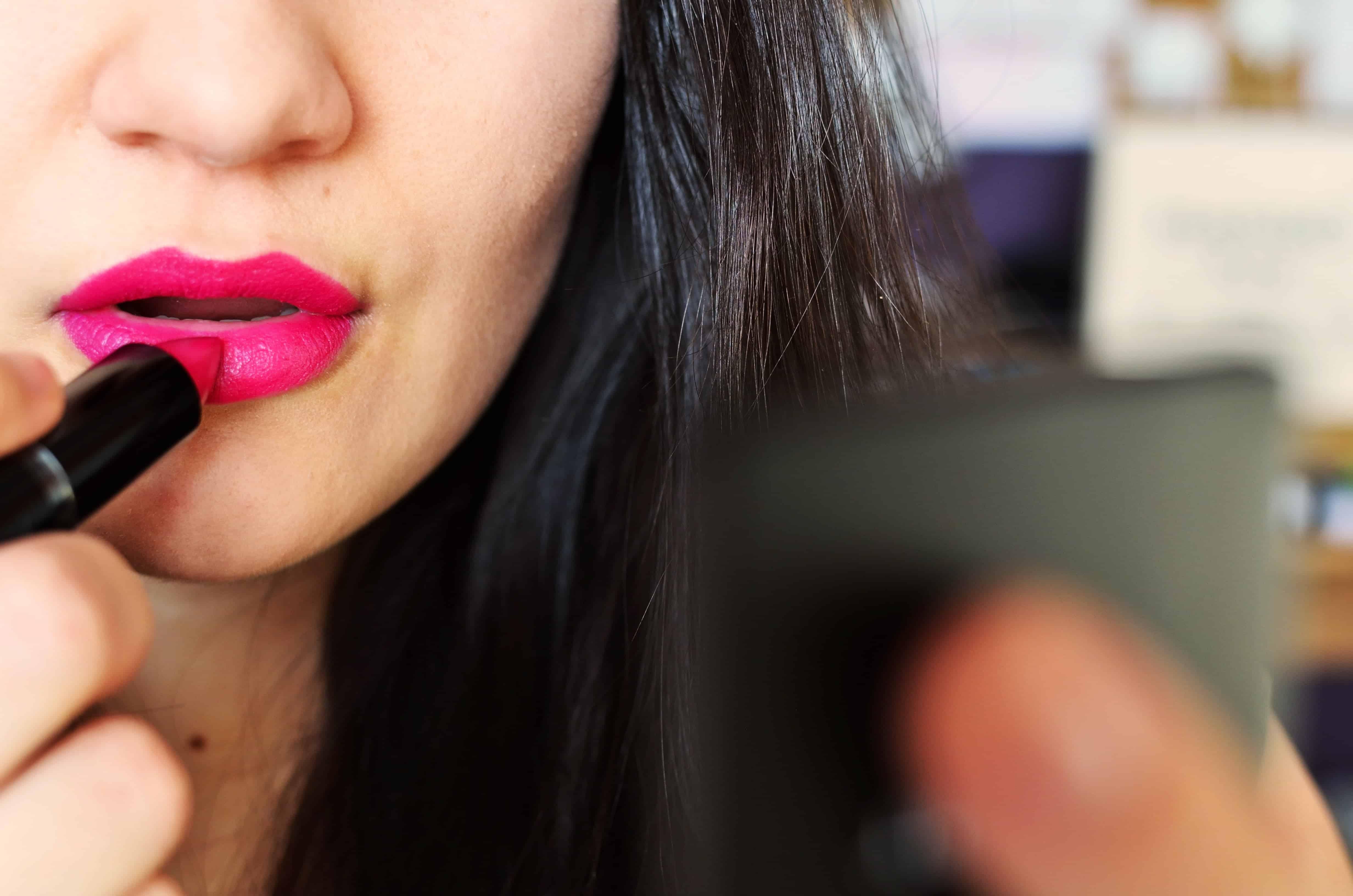 Frau traegt pinken Lippenstift auf