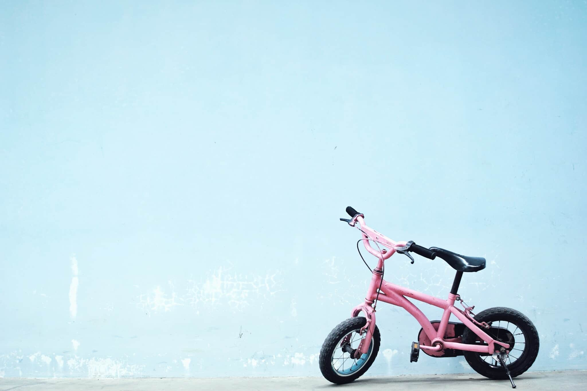 rosa Kinder-Fahrrad vor blauem Grund