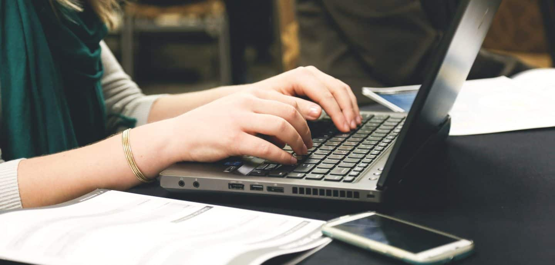 Maedchen sitzt am Tisch mit Laptop und Smartphone