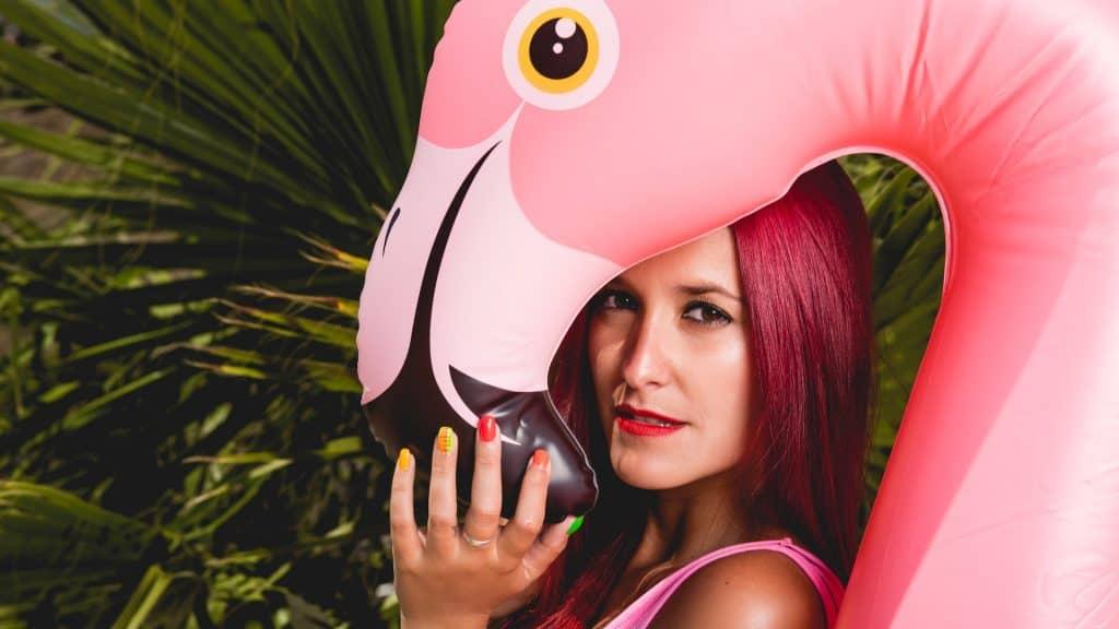 Frau posiert mit aufblasbarem Flamingo