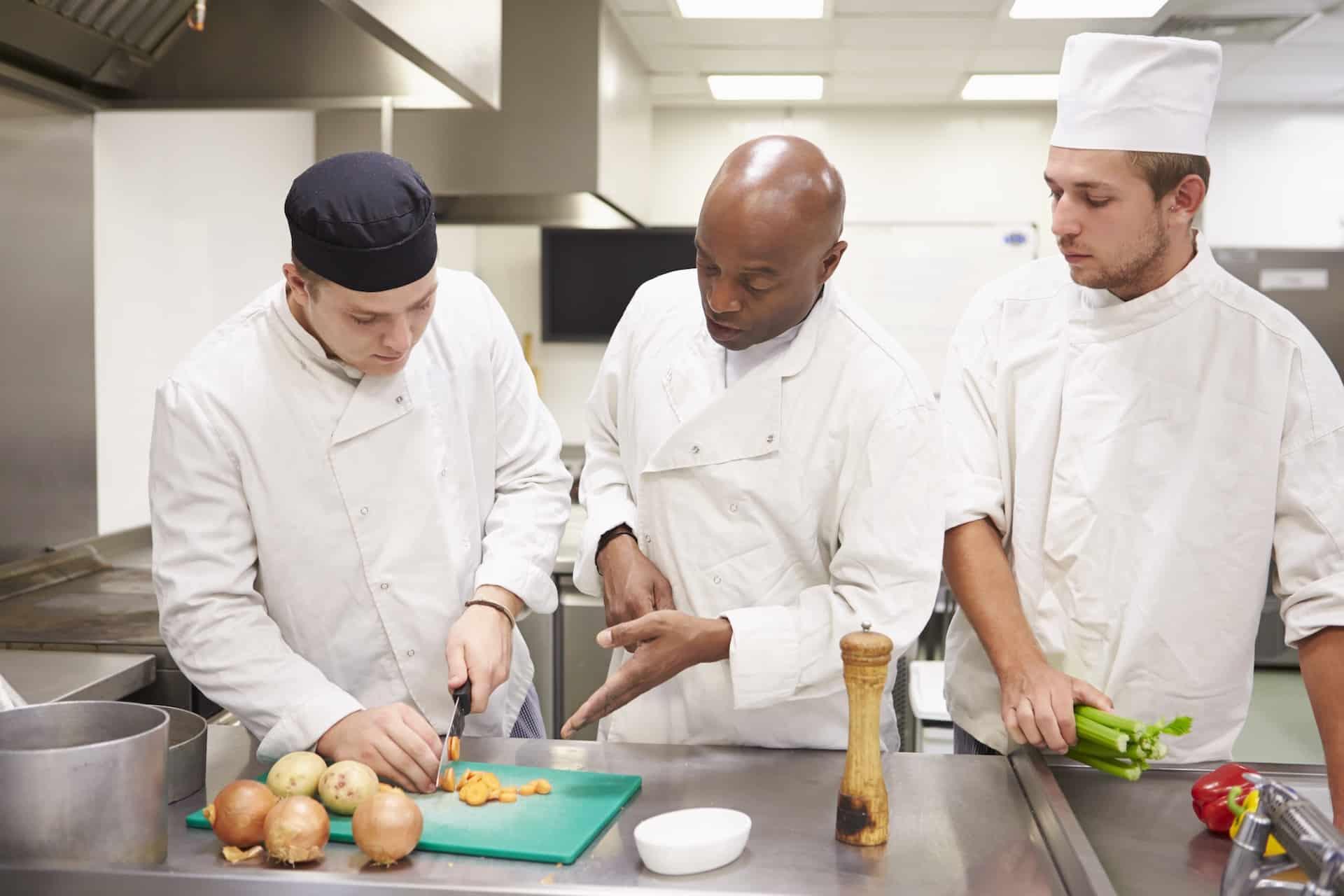 Ein Koch zeigt zwei Auszubildenden, wie man schneidet