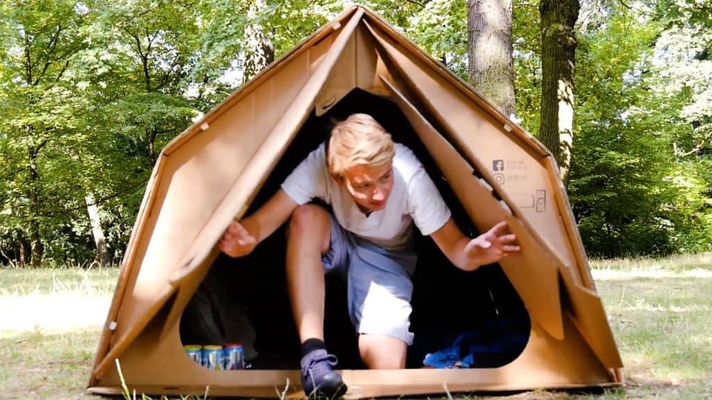 Junger Mann kommt aus Zelt aus Pappe