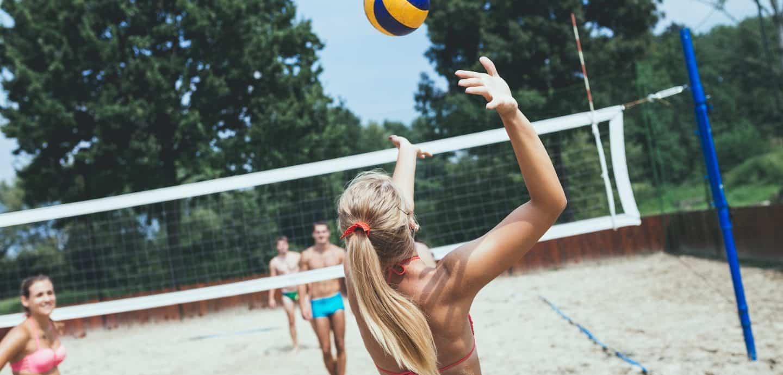 Junge Menschen spielen Beachvolleyball