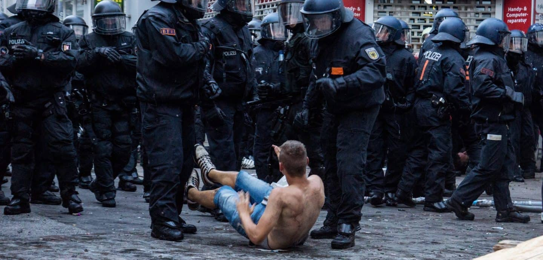 Ein Demonstrant liegt vor Polizisten beim G20-Gipfel