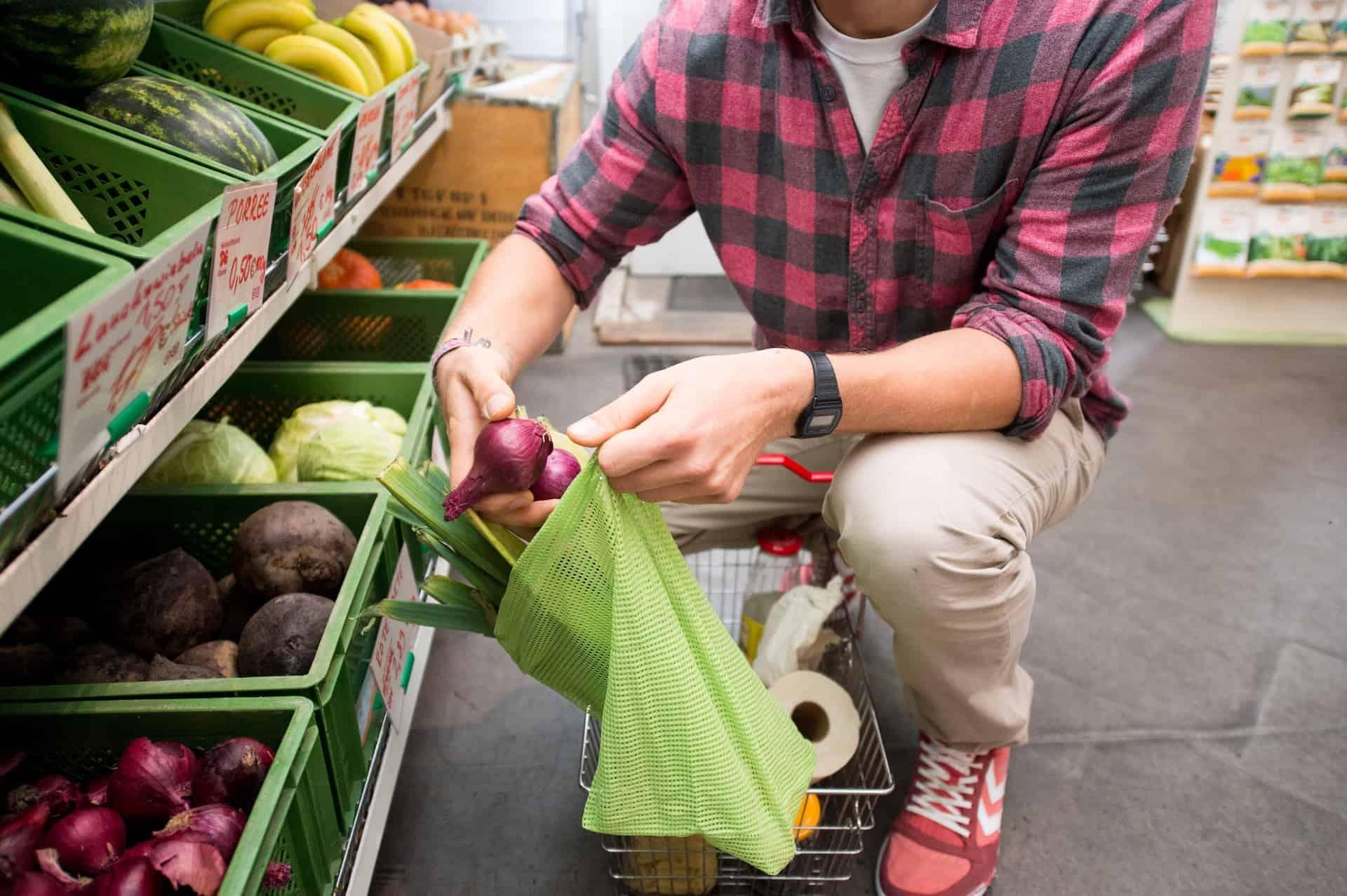 Ein Mann packt Zwiebeln in einen plastikfreuen Einkaufsbeutel.