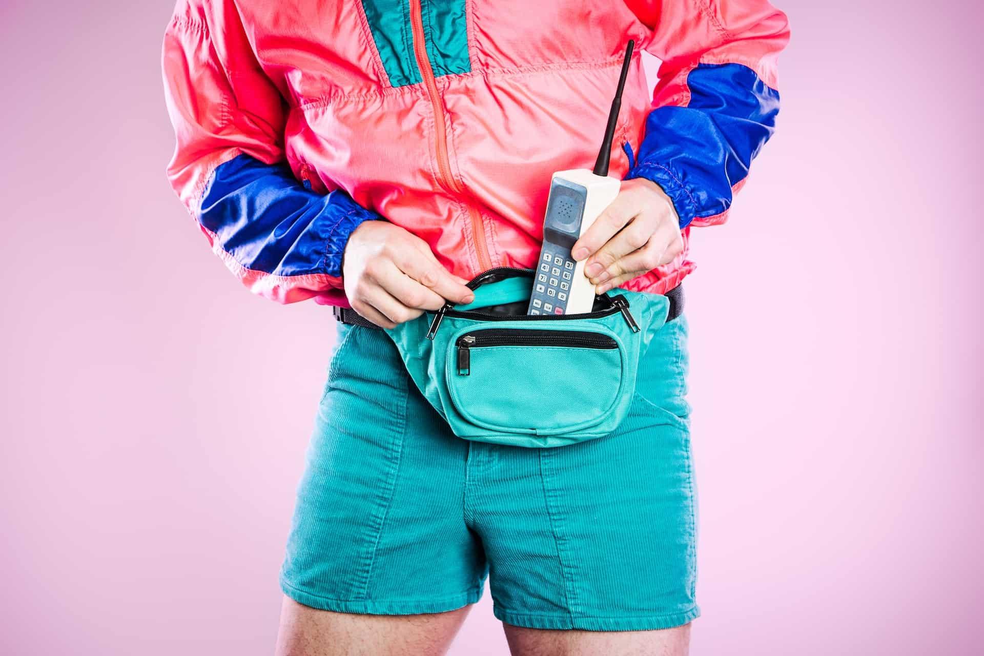 Ein Mann im 80er Jahre Style packt ein altes Handy in seine Gürteltasche.
