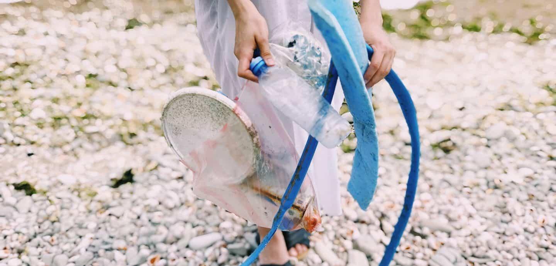 Eine Person am Strand haelt Plastikmuell in der Hand