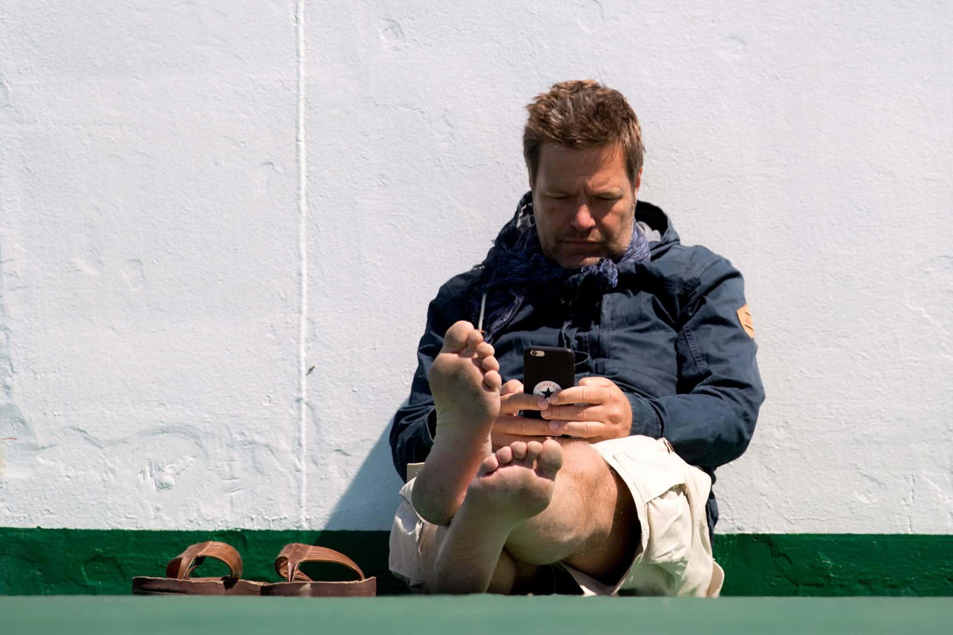 Robert Habeck sitzt mit seinem Handy in der Hand