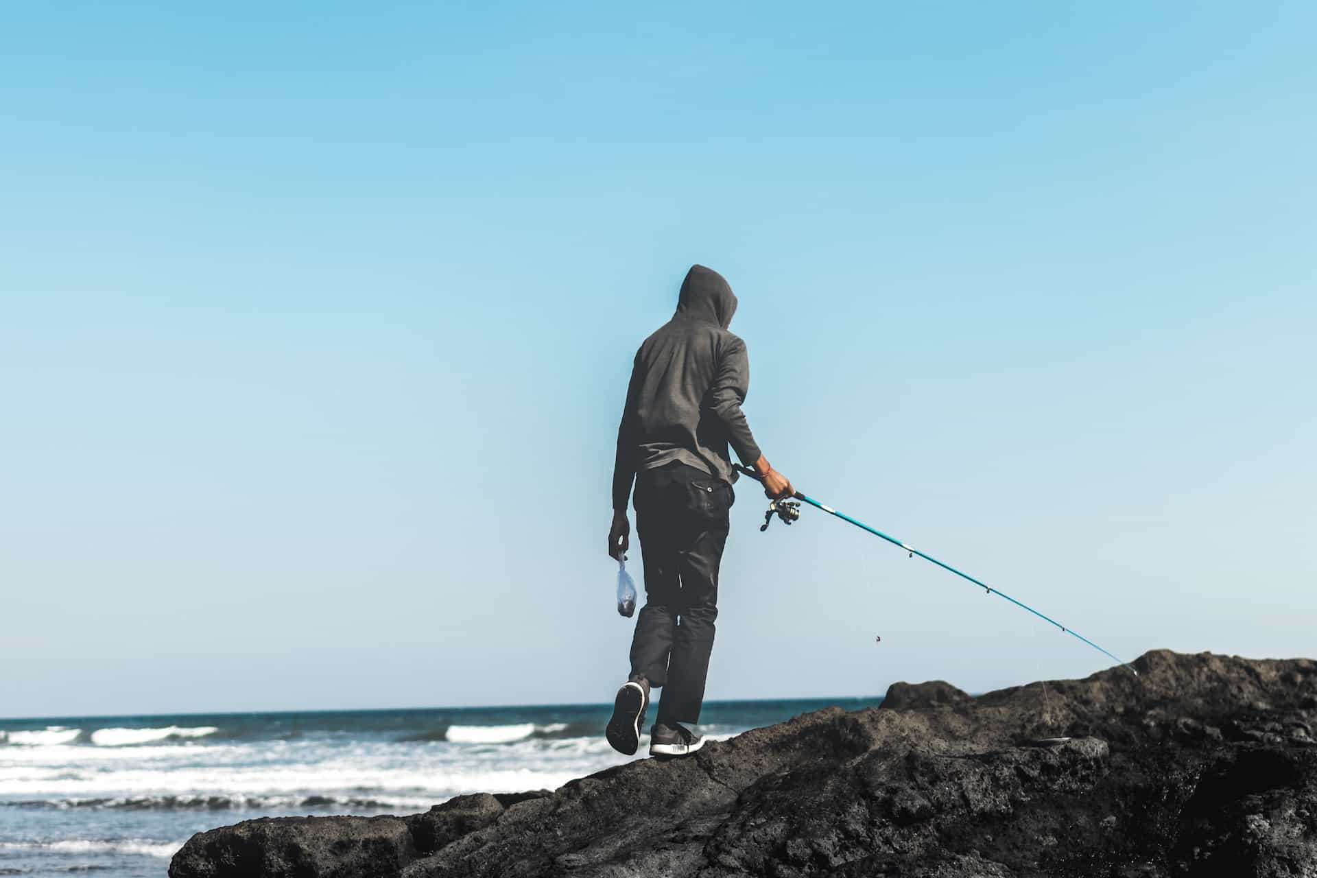 Junger Mann steht mit Ruecken zur Kamera und einer Angel am Meer