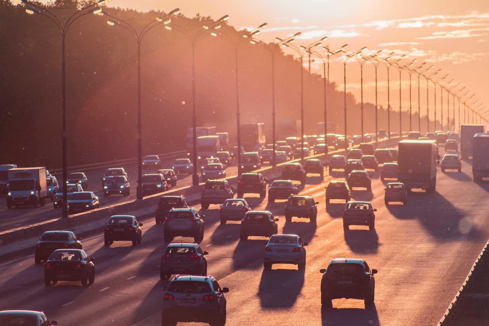 Autos und Smog im roetlichen Abendlicht