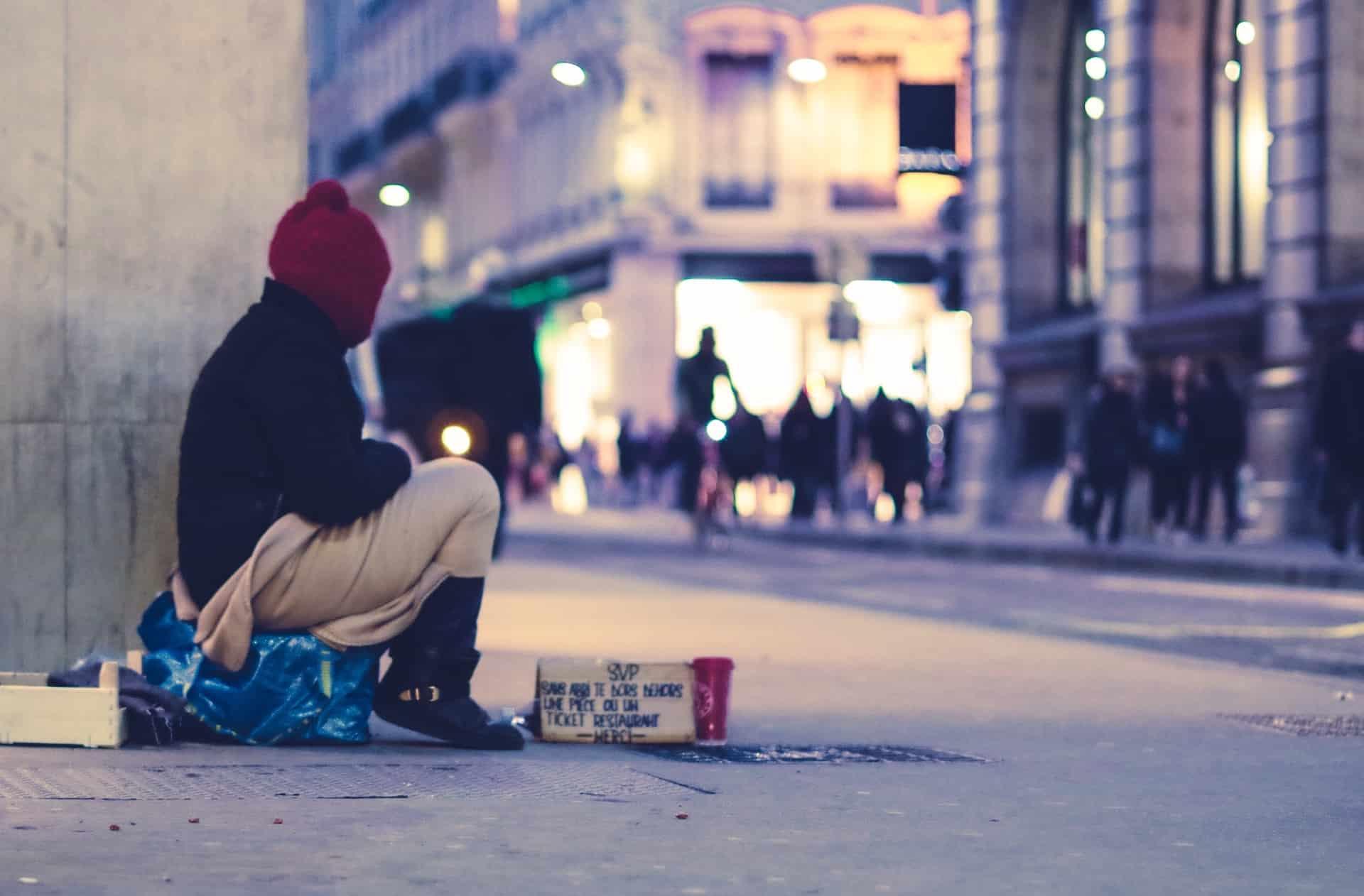 Obdachloser sitzt auf einer Einkaufsstraße