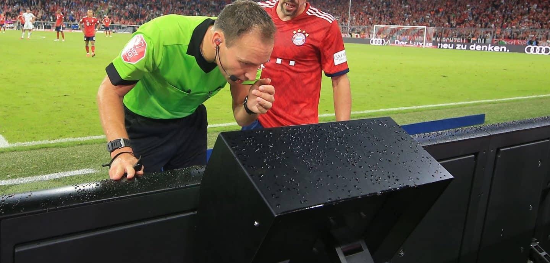 Ein Schiedsrichter lässt sich vom Videobeweis helfen
