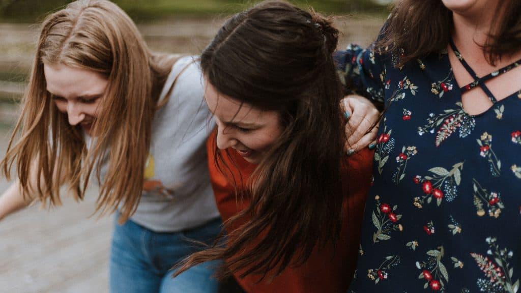 drei Freundinnen liegen sich in den Armen und lachen