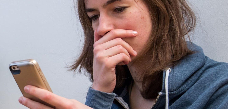 Mädchen guckt entsetzt auf ihr Handy (c) dpa