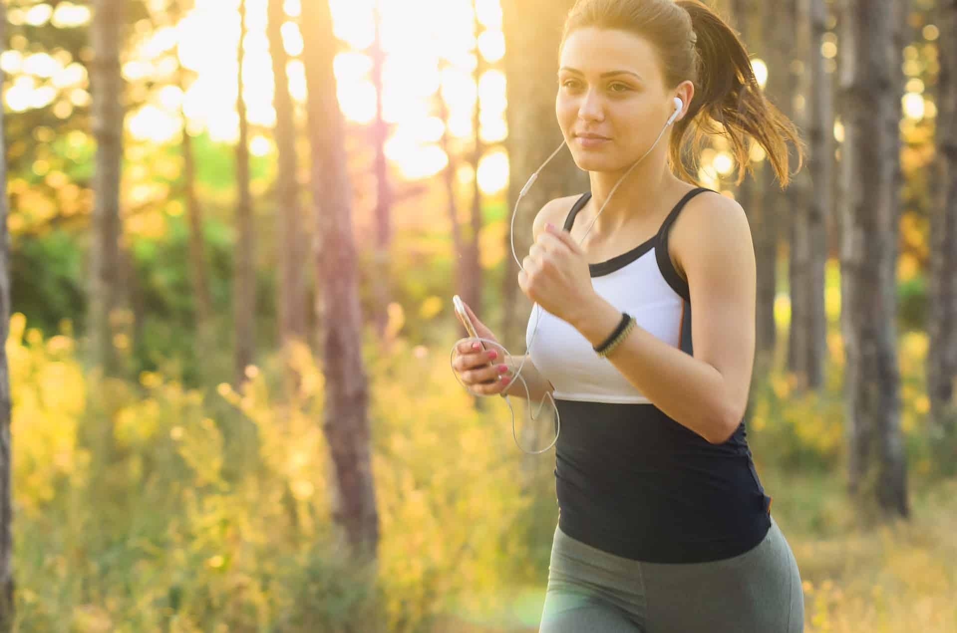 Eine Frau joggt im Gruenen und hat Kopfhoerer im Ohr (c) Pixabay