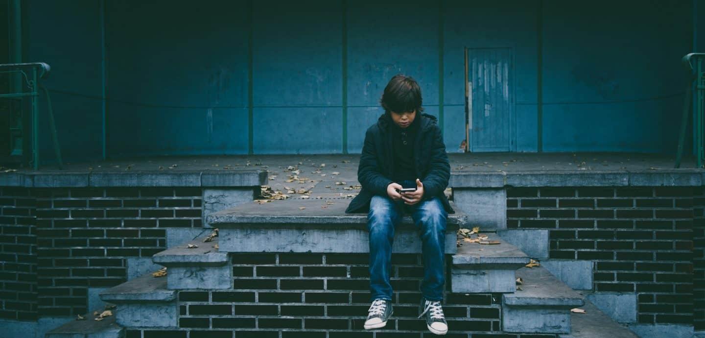 Junge sitzt alleine mit Smartphone auf Treppe