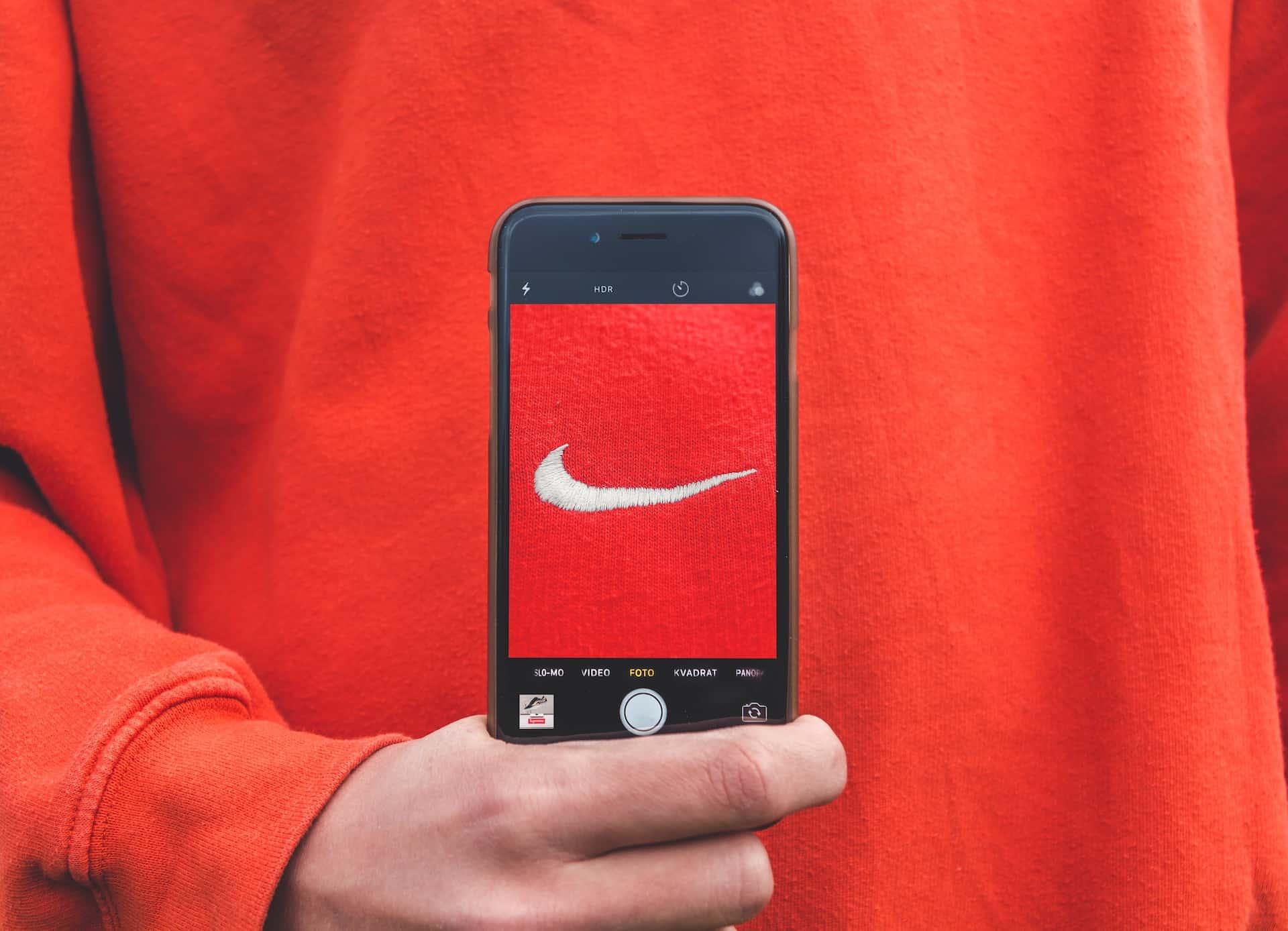 Jemand macht ein Foto von dem Nike-Logo auf seinem roten Pullover