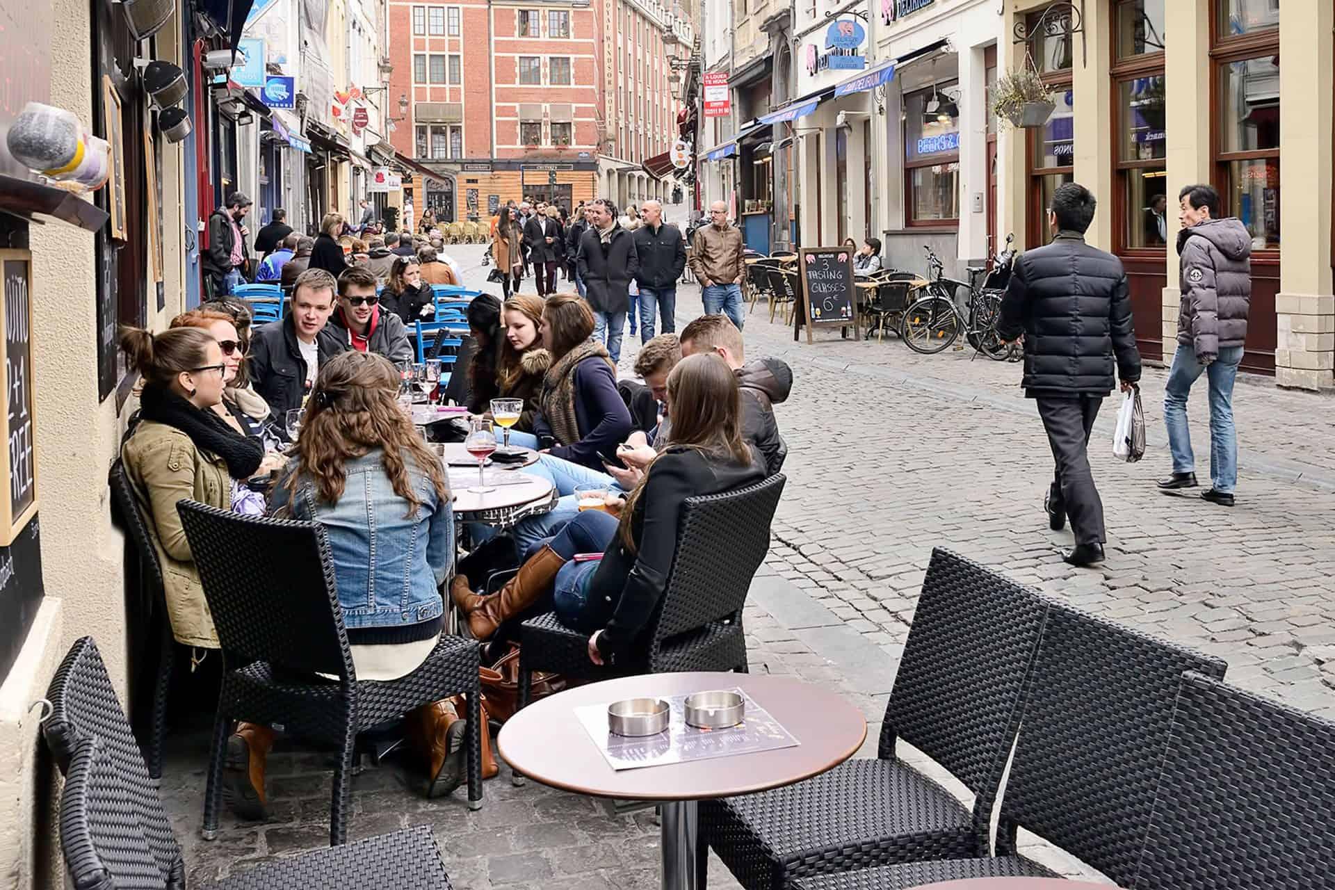 Junge Europäer sitzen vor einem Café auf der Straße
