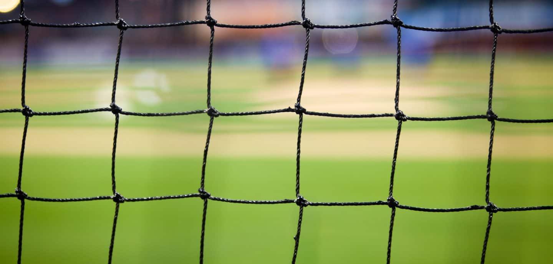 Blick durch ein schwarzes Netzt auf ein Fußball-Feld