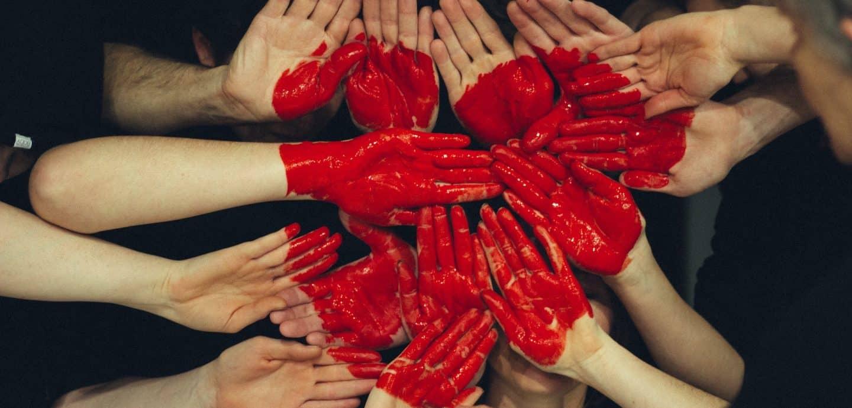 auf einen Haufen Haende wurde ein rotes Herz gemalt