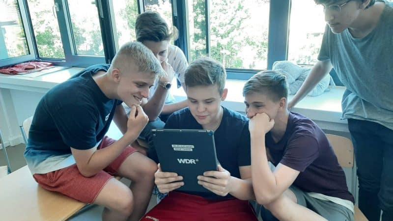 Fünf Schüler schauen auf ein iPad